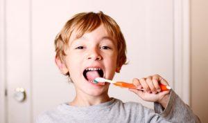 Bambino che lava i denti per prevenire le carie