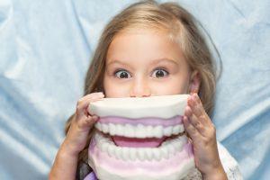 Una bambina che gioca con una dentiera