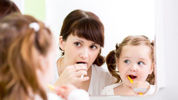 La mamma e il bambino lavano i denti