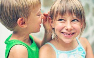 Un bambino parla all'orecchio di una bambina