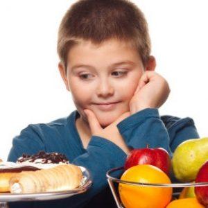 Un bambino indeciso tra dolci e frutta